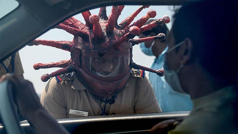 Policial usa capacete de coronavírus